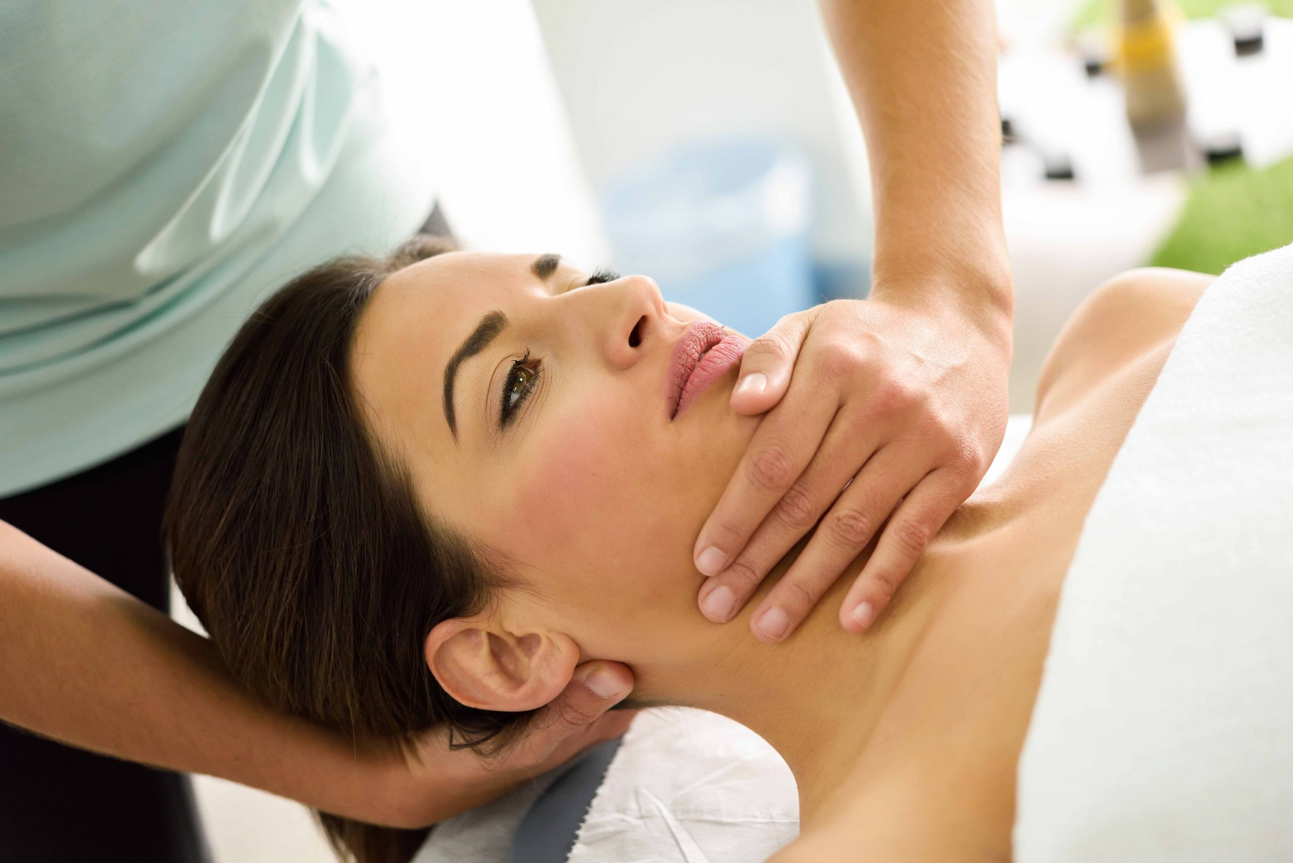 Young caucasian woman receiving a head massage in a spa center. Female patient is receiving treatment by professional therapist.