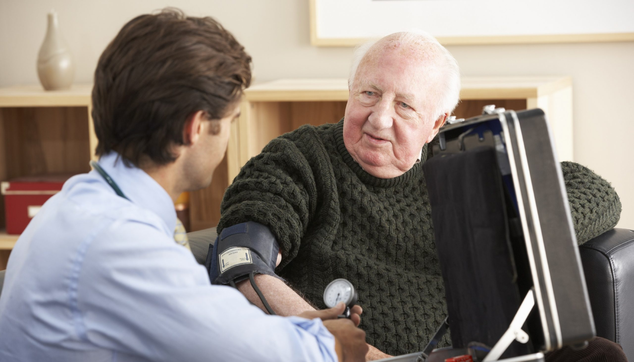 Doctor taking senior man's blood pressure at home